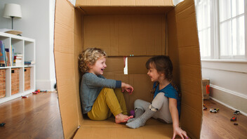 Children playing indoor. Brother and sister playing together inside a cardboard box on the floor. People, children, kids, siblings, playing,